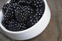 Ripe blackberries in white bowl on old oak table stock photo