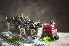 Ripe blackberry and blackberry jam on a wooden table. Dark background. Selective focus. Background with copy space stock photography