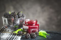 Ripe blackberry and blackberry jam on a wooden table. Dark background. Selective focus. Background with copy space stock images