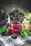 Ripe blackberry and blackberry jam on a wooden table. Dark background. Selective focus royalty free stock photography