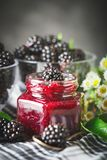Ripe blackberry and blackberry jam on a wooden table. Dark background. Selective focus royalty free stock image
