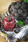 Ripe blackberry and blackberry jam on a wooden table. Dark background. Selective focus royalty free stock photos