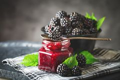 Ripe blackberry and blackberry jam on a wooden table. Dark background. Selective focus stock photos