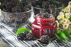 Ripe blackberry and blackberry jam on a wooden table. Dark background. Selective focus stock image
