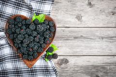 Ripe blackberry and blackberry jam on a wooden table. Top view. Selective focus. Background with copy space royalty free stock photos