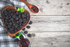 Ripe blackberry and blackberry jam on a wooden table. Top view. Selective focus. Background with copy space royalty free stock images