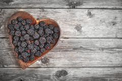 Ripe blackberry and blackberry jam on a wooden table. Top view. Selective focus. Background with copy space royalty free stock image