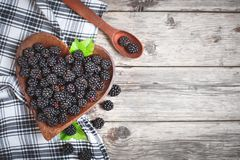 Ripe blackberry and blackberry jam on a wooden table. Top view. Selective focus. Background with copy space stock photo