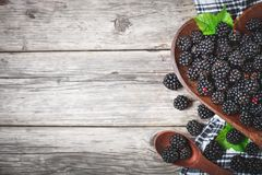 Ripe blackberry and blackberry jam on a wooden table. Top view. Selective focus. Background with copy space royalty free stock photography