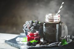 Ripe blackberry, blackberry juice and jam on a wooden table. Dark background. Dark background. Selective focus. Background with copy space stock image