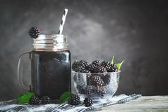 Ripe blackberry and blackberry juice on a wooden table. Dark background. Dark background. Selective focus. Background with copy space royalty free stock images