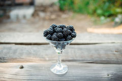 Ripe blackberry in a glass on wooden boards. Organic blackberries in a glass on a gray wooden board, rustic, detox,selective focus Royalty Free Stock Photos