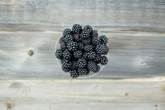 Ripe blackberry in a glass on wooden boards. Organic blackberries in a glass on a gray wooden board, rustic, detox,selective focus Royalty Free Stock Photography