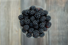 Ripe blackberry in a glass on wooden boards. Organic blackberries in a glass on a gray wooden board, rustic, detox,selective focus Stock Photos
