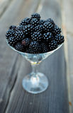 Ripe blackberry in a glass on wooden boards. Organic blackberries in a glass on a gray wooden board, rustic, detox,selective focus Royalty Free Stock Image