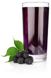 Ripe blackberry with green leaf and juice in glass Royalty Free Stock Images