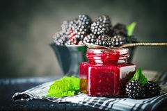 Ripe blackberry and blackberry jam on a wooden table. Dark background. Selective focus stock photography
