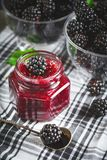 Ripe blackberry and blackberry jam on a wooden table. Dark background. Selective focus stock images
