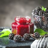 Ripe blackberry and blackberry jam on a wooden table. Dark background. Selective focus. Background with copy space royalty free stock photography