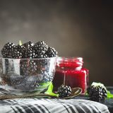 Ripe blackberry and blackberry jam on a wooden table. Dark background. Selective focus. Background with copy space stock image