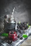 Ripe blackberry, blackberry juice and jam on a wooden table. Dark background. Dark background. Selective focus. Background with copy space royalty free stock photo