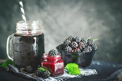Ripe blackberry, blackberry juice and jam on a wooden table. Dark background. Dark background. Selective focus. Background with copy space stock images