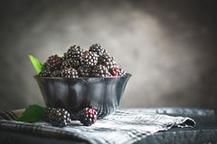 Ripe blackberry on a wooden table. Dark background. Selective focus. Background with copy space stock photo