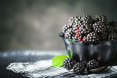 Ripe blackberry on a wooden table. Dark background. Selective focus. Background with copy space royalty free stock photo