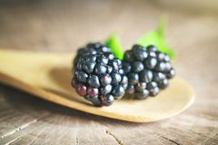 Ripe blackberry on a wooden table. Dark background. Selective focus. Background with copy space stock photography