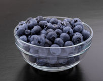 Ripe blueberries in bowl on black Stock Image