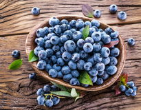 Ripe blueberries in the bowl on the wood. Stock Photography