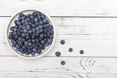 Ripe blueberries in a plate on a white wooden table. Top view. Copy space royalty free stock images