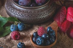 Ripe blueberries and raspberries lie in a handmade ceramic pot and a wooden spoon with a beautiful autumn leaf. Close up Stock Image