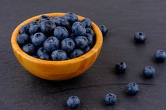 Ripe blueberries in wooden bowl on black stone table background. Side view royalty free stock images