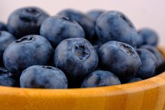 Ripe blueberries in wooden bowl. Close up view royalty free stock photos
