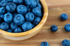 Ripe blueberries in wooden bowl on wood table background. Side view stock image