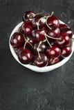 Ripe bright cherries in white plate. Ripe cherry berries in white plate on concrete background Stock Photo