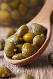 Ripe capers in a wooden spoon closeup on old table. Royalty Free Stock Photo