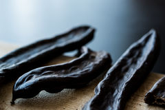 Ripe Carob Pods on wooden surface. royalty free stock photography