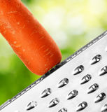 Ripe carrot rubbing on a grater Stock Photography