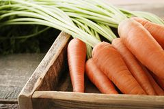 Ripe carrots. Fresh and ripe carrots in crate on wooden table Stock Images