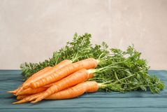 Ripe carrots on wooden table against light background stock image