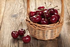 Ripe cherries in a basket on an old board Stock Images