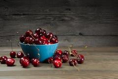 Ripe cherries in bowl on barn wood Stock Photos