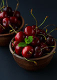Ripe cherries in a clay bowl on black background Stock Images
