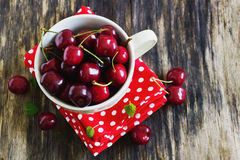 Ripe cherries in a cup. On the old wooden background. top view . rustic style. health and diet concept Royalty Free Stock Image