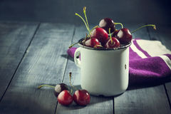 Ripe cherries in an iron mug on a dark blue wooden background. Stock Photo