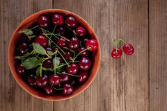 Ripe cherries with leaves in bowl on old wooden rustic backgroun Stock Photo