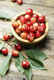 Ripe cherries with leaves on a wooden background, in a wooden pl Stock Photo