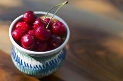 Ripe cherries in a rustic recipient. Stock Photos